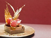 Small chocolate cake with raspberries and caramel fans