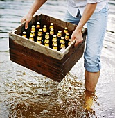 Man lifting a crate of beer out of water