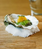 Oyster with cucumber and mango on a bed of salt