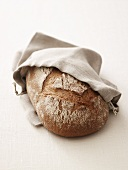 Brown bread (made with wheat and rye flour) in linen bag