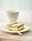 A piece of mandarin orange cake with poppy seeds