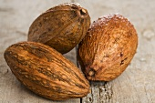 Three cocoa pods on wooden background