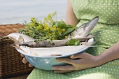 Woman holding bowl of freshly caught fish and herbs