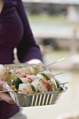 Woman holding raw fish & vegetable kebabs in aluminium dish