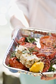 Woman holding grilled fish kebab & tomatoes in aluminium dish