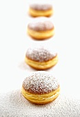 Four doughnuts sprinkled with icing sugar in a row