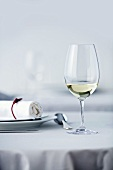 Glass of white wine on table laid in white