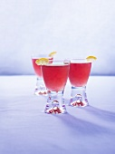 Three pomegranate drinks with pieces of lemon