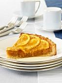 Ein Stück Orangen-Mandel-Tarte auf Tellerstapel