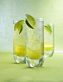 Three Drambuie Sodas with ice cubes and lime wedges