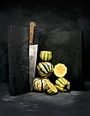 Whole and halved acorn squashes with a knife