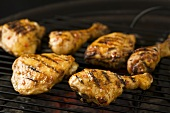 Marinated chicken drumsticks and thighs on a barbecue