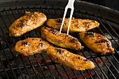 Marinated chicken breasts on a barbecue