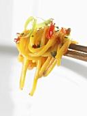 Egg noodles with vegetables on chopsticks (Asia)