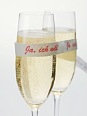 Two glasses of sparkling wine with ribbon ('I do' in German)