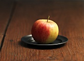 An Elstar apple on a pewter plate