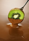 A slice of kiwi fruit in chocolate sauce