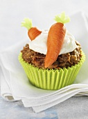 Carrot muffin with marzipan carrots and cream topping