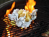 Baked potato with butter on a barbecue