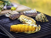 Corn on the cob, lamb chops and artichoke on a barbecue