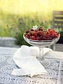 Berries & cherries in crystal pedestal bowl on table outdoors