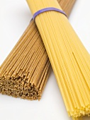 Bundle of durum wheat spaghetti on bundle of wholemeal spaghetti