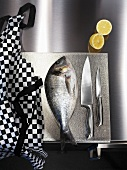 Sea bream, kitchen knives and apron on chopping board