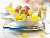 Easter place-setting with coloured egg and flowers