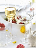 Glass of sparkling wine & empty wine glasses on Easter table