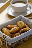 Madeleines in bread basket in front of cup of coffee