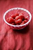 Several raspberries in a crystal bowl