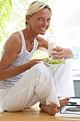 Woman with plate of salad and glass of milk