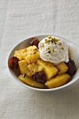 Stewed pineapple with orange and scoop of ice cream