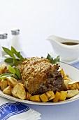Leg of lamb with mustard crust on roast potatoes