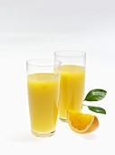Two glasses of orange juice, wedge of orange and leaves