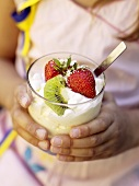 Child's hands holding soft vanilla ice cream with fruit