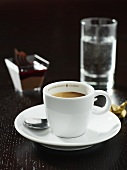 A cup of espresso with a glass of water