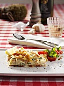 Piece of salmon lasagne garnished with tomato and basil