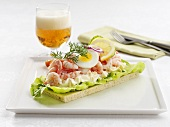 Shrimp and egg open sandwich with dill, glass of beer