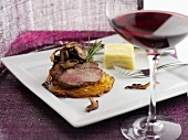 Beef fillet on rösti with mushrooms, glass of red wine