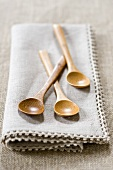Three wooden spoons on fabric napkin
