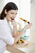 Young woman eating fruit skewer
