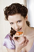 Young woman eating crispbread with salmon