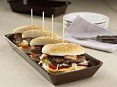 Four hamburger halves with bacon in a row
