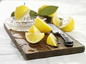 Pieces of lemon with squeezer on wooden board