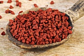 Annatto seeds on a wooden spoon