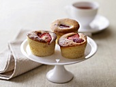 Three strawberry buns on cake stand