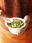 Woman holding bowl of chicken noodle soup