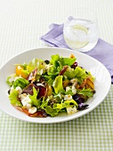 Salad leaves with peach wedges, ham and feta
