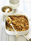 Apple and walnut crumble in a baking dish and small bowl
